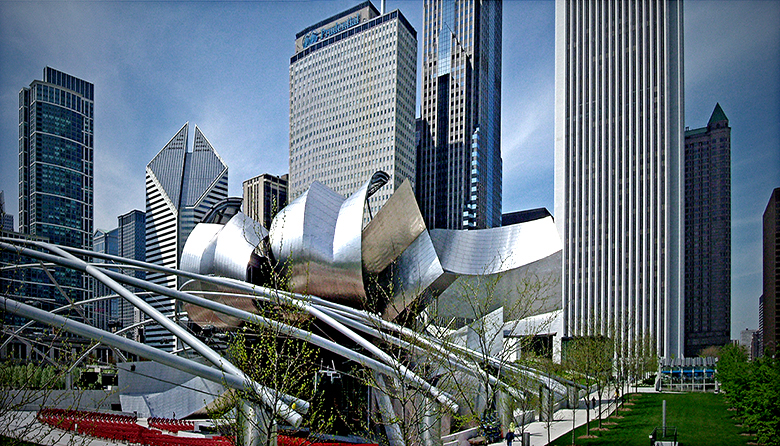 Millenium Park Chicago - Grant Park in downtown Chicago showing the Frank Gehry bandshell of the Pritzger Pavilion in Millennium Park bandshell, the Standard Oil building and surrounding office and hotel buildings